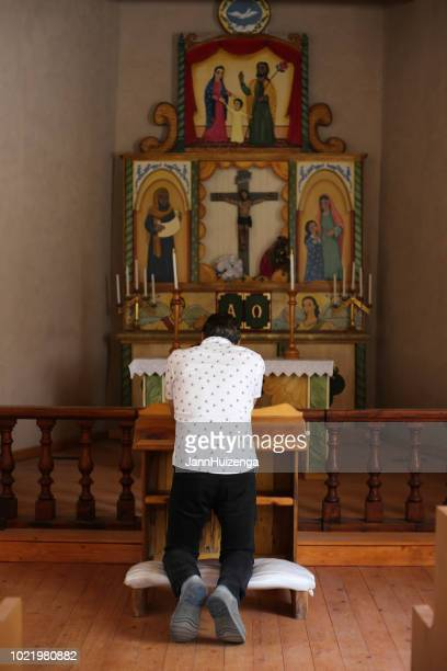 man kneeling and praying in rustic new mexican church - altar stock pictures, royalty-free photos & images