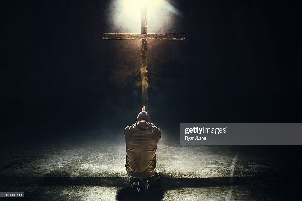 Man Kneeling Before the Cross : Stock Photo