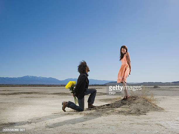 man kneeling in front of woman in desert, holding bouquet, side view - kneeling stock pictures, royalty-free photos & images