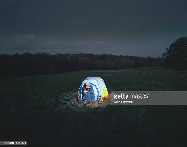 man kneeling in tent doorway shining torch, night - dome stock pictures, royalty-free photos & images