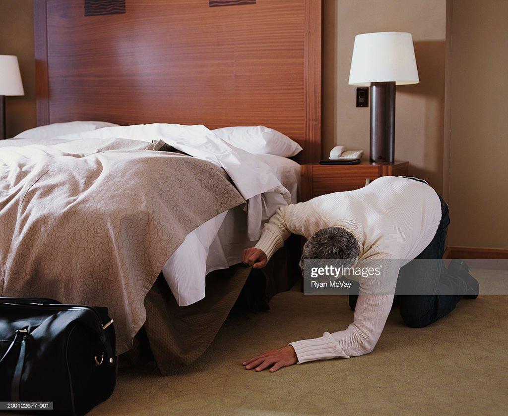 Man Kneeling On Floor In Hotel Room Looking Under Bed High