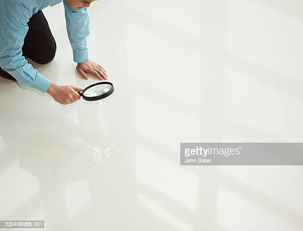 Man kneeling on floor looking through magnifying glass, elevated view