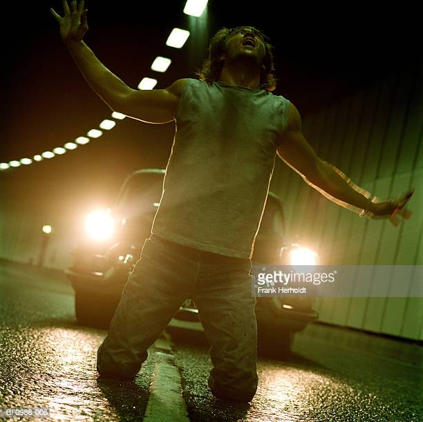 Man kneeling on road in front of car, arms outstretched, close-up