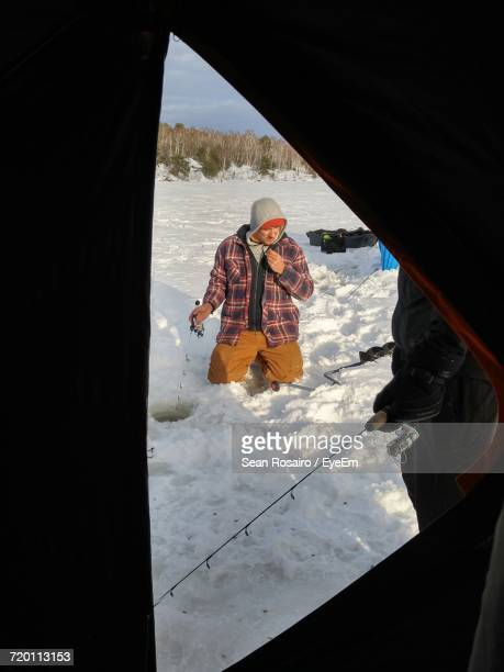 man kneeling on snow covered field seen through tent - sudbury canada stock photos and pictures