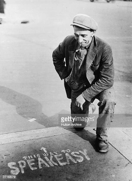 A man kneeling on the pavement next to a sign showing the way to a speakeasy during the Prohibition in America