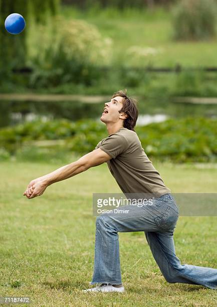 Man kneeling to hit volleyball