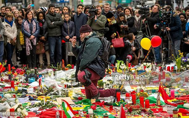 TOPSHOT A man kneels and makes the sign of the cross during a minute of silence held at a makeshift memorial in front of Brussel's Stock Exchange on...