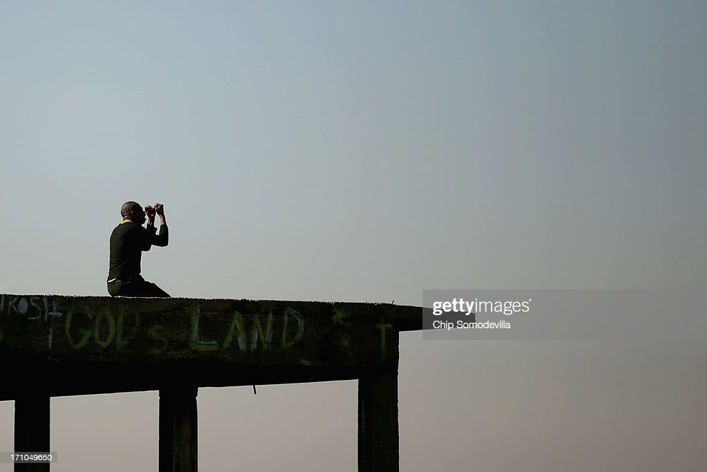 A man kneels and prays on top of an unfinished building on a hill overlooking downtown in the Yeoville neighborhood June 21, 2013 in Johannesburg, South Africa. The worn, arid space on top of the Yeoville hill offers worshipers of various Christian denominations from South African, Botswana, Zimbabwe, the Democratic Republic of Congo and other African nations an open-air space where they can publicly practice their faith with a scenic view of downtown Johannesburg.