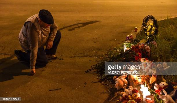 A man kneels as he lays flowers near a college in Kerch Crimea on October 17 after a student opened fire at a technical college in the Russianannexed...