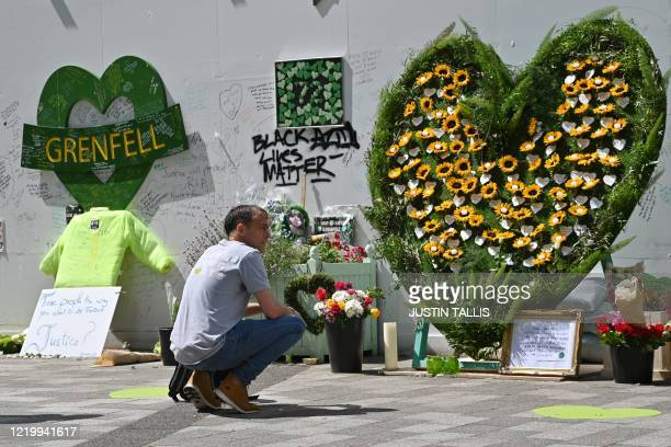 A man kneels as he pays his respects in front of floral tributes left near to Grenfell tower in west London on June 14 on the third anniversary of...