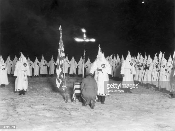 A man kneels at a burning cross as a hooded Klan member stands over him with a chalice during a Ku Klux Klan nighttime initiation ceremony 1920s...