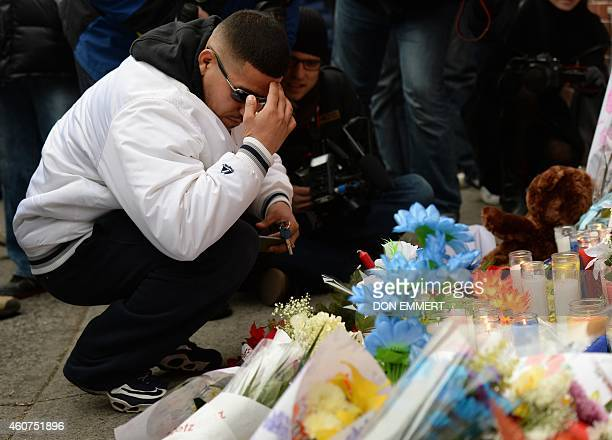 A man kneels at a memorial near Tompkins Ave and Myrtle Ave December 21 2014 in New York near the site where two New York City police officers were...