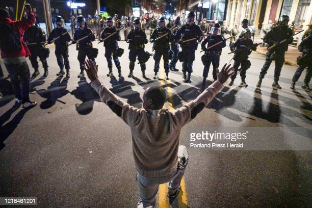 Man kneels before a line of police in riot gear on Middle Street in Portland during a protest on Tuesday night.