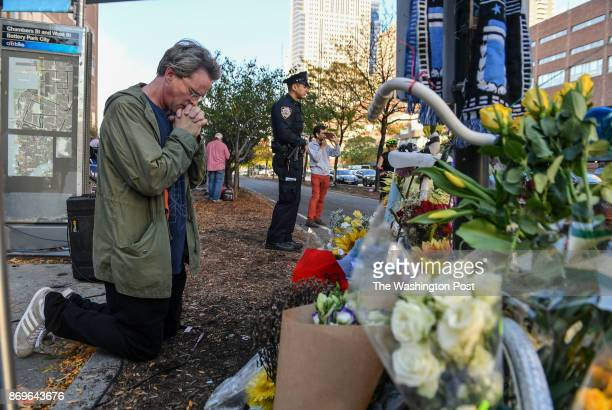 A man kneels down and prays at a previous bicycle memorial which is now being used as a memorial for the deadly attack two days ago when Sayfullo...