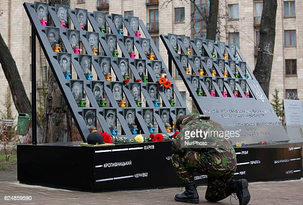A man kneels down during a commemoration ceremony at the monument to the socalled quotNebesna Sotnyaquot the people killed during the Ukrainian...