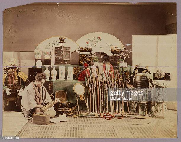 A man kneels holding an abacus in a shop which displays swords armor fans and lacquer items Japan ca 1880s1890s