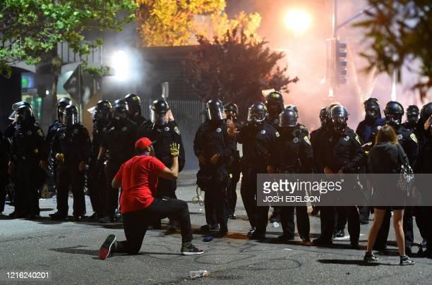 Man kneels in front of a police skirmish line in Oakland California on May 29, 2020. - Violent protests erupted across the United States late on May...