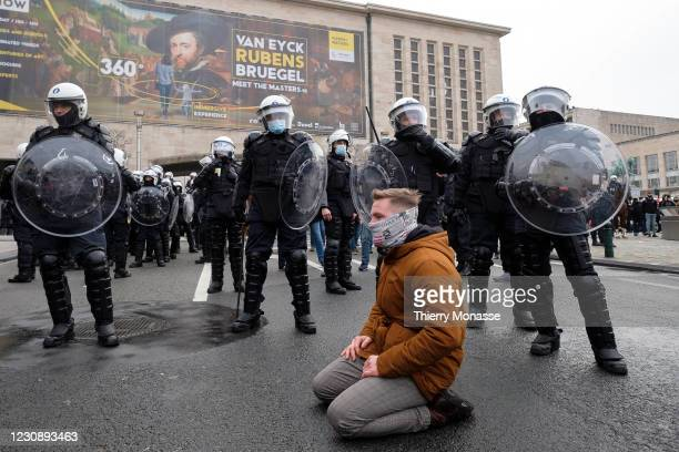 Man kneels in front of police as people take part in a protest against government-imposed measures to tackle the coronavirus pandemic as police take...