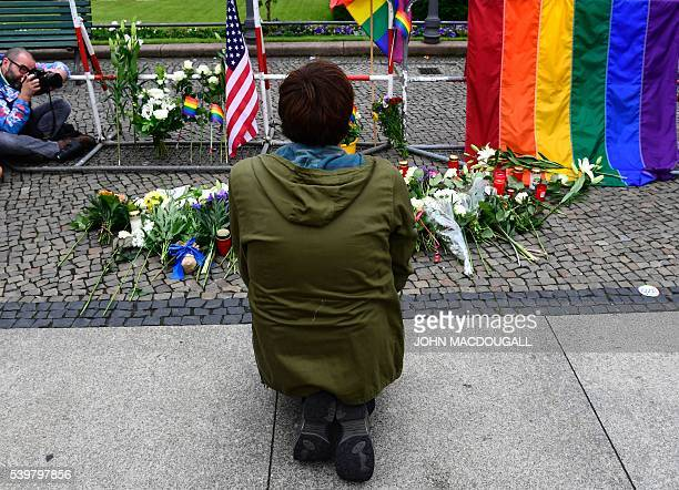 A man kneels near flowers candles US and rainbow flags in front of the US embassy in Berlin on June 13 2016 as people pay tribute to the victims of...