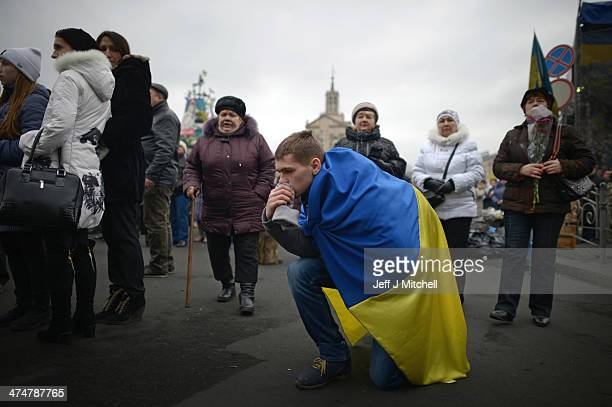 A man kneels on the ground draped in a Ukrainian flag during a funeral of an antigovernment demonstrator in Independence square where dozens of...