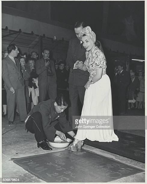 A man kneels to help Carmen Miranda make a footprint in the cement at Mann's Chinese Theater in Hollywood California