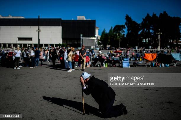 Man kneels to pray at the Fatima shrine in Fatima, central Portugal, on May 12, 2019. - Thousands of pilgrims converged on the Fatima Sanctuary to...