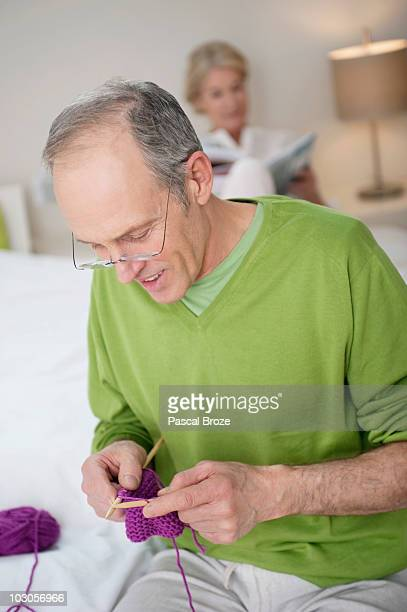 Man knitting with a woman in the background