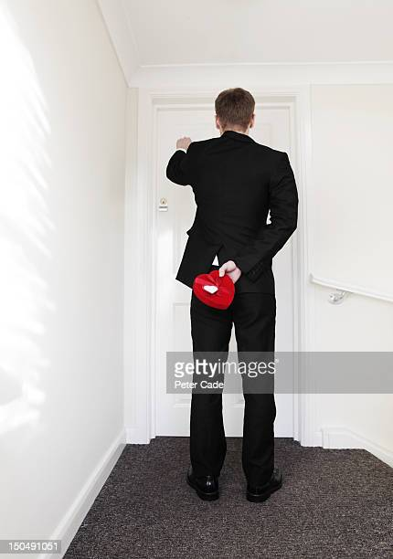 man knocking on door holding heart shaped box - knocking on door stock photos and pictures