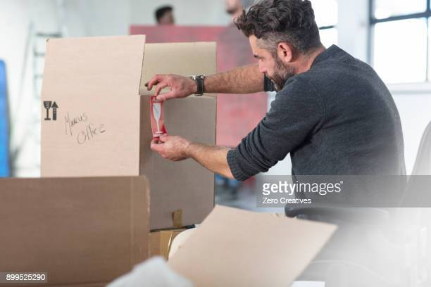 man labelling cardboard boxes - labeling stock photos and pictures