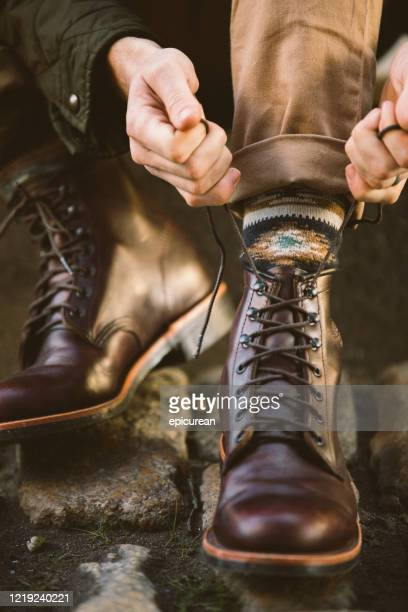man lacing up a leather boot - leather shoe stock pictures, royalty-free photos & images