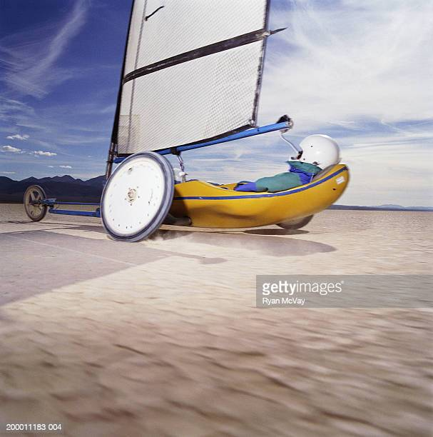 Man land yachting on dry lake bed, side view (blurred motion)