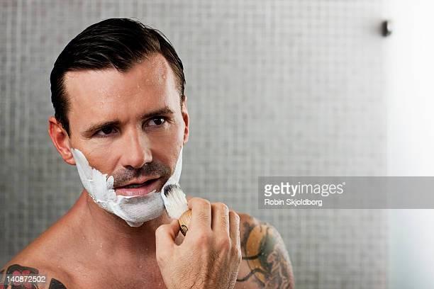 Man lathering shaving cream on face