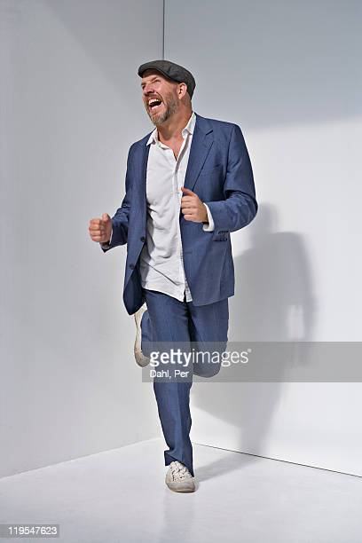 Man laughing and running against white background