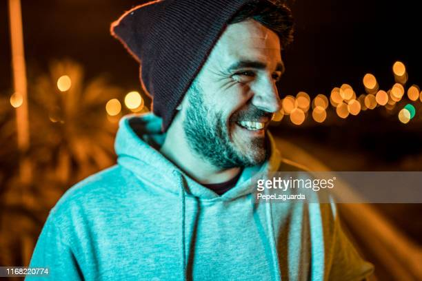 man laughing and wearing casual clothes and a wool hat at night - one man only stock pictures, royalty-free photos & images