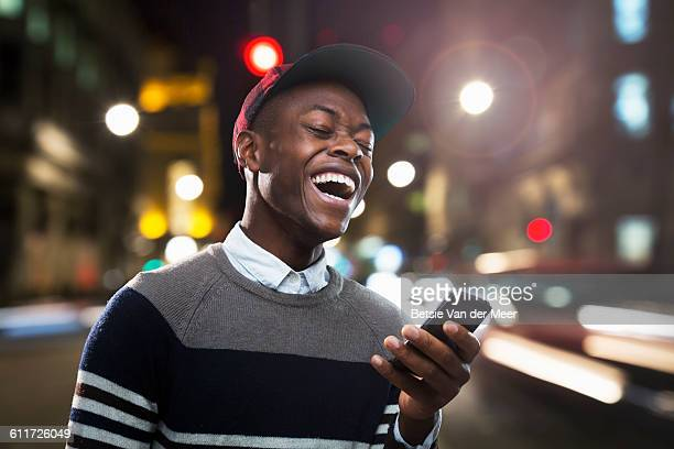 man laughing at phone in urban street at night. - facebook stock pictures, royalty-free photos & images