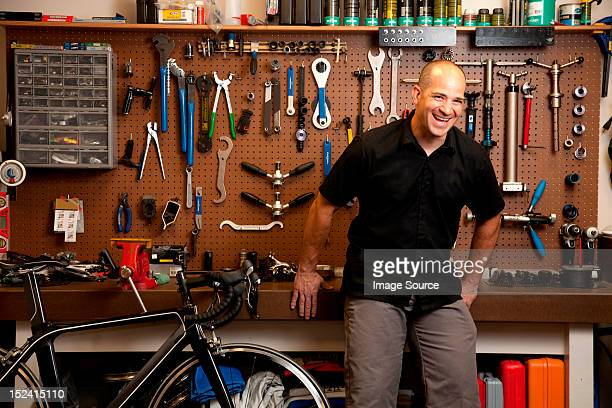 Man laughing in bicycle repair shop