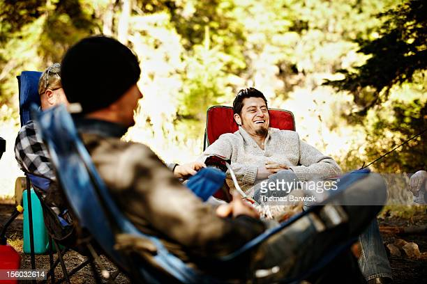 Man laughing in discussion with friends camping