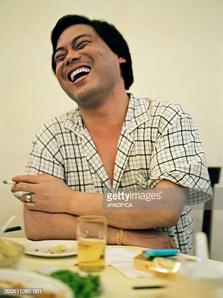 Man laughing, smoking cigarette, having drink in restaurant