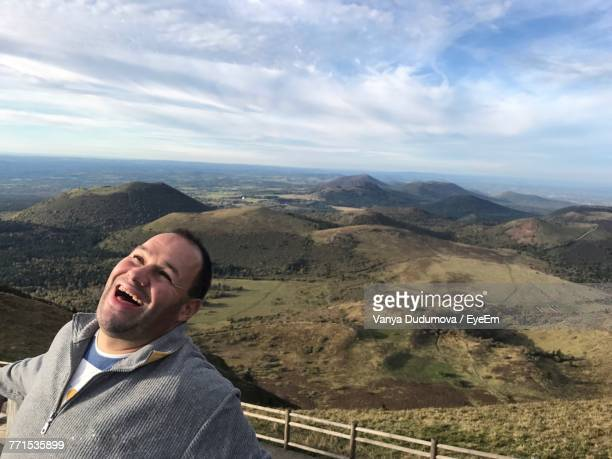 Man Laughing While Standing Against Mountains