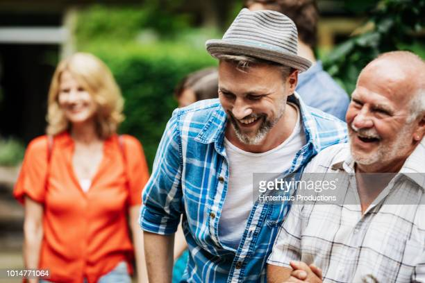 man laughing with father during family bbq - part of a series stock pictures, royalty-free photos & images
