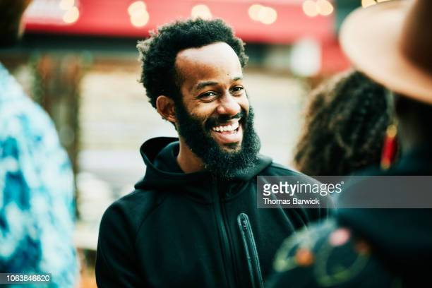 man laughing with friends during party at outdoor bar - 30 39 years stock pictures, royalty-free photos & images