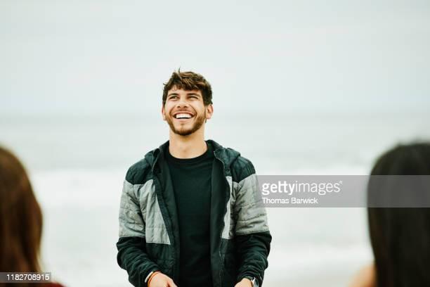 man laughing with friends during summer beach party - só um homem jovem - fotografias e filmes do acervo