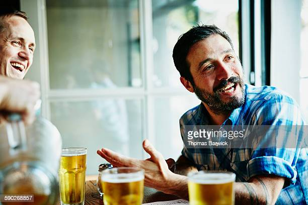 Man laughing with friends over beers in restaurant