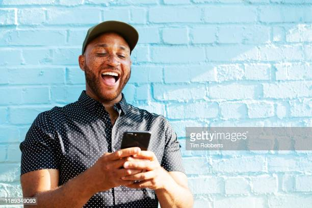 man laughing with smart phone - alegria imagens e fotografias de stock