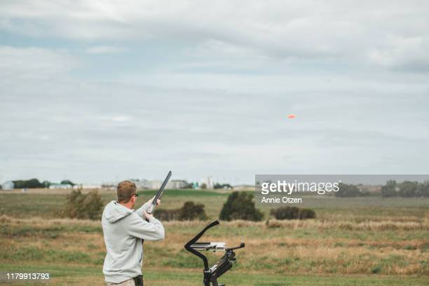 man launching clay pigeons - clay pigeon shooting stock pictures, royalty-free photos & images