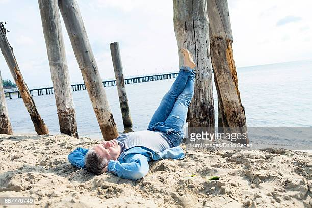 man laying down on beach with feet up - lazy poland stock photos and pictures