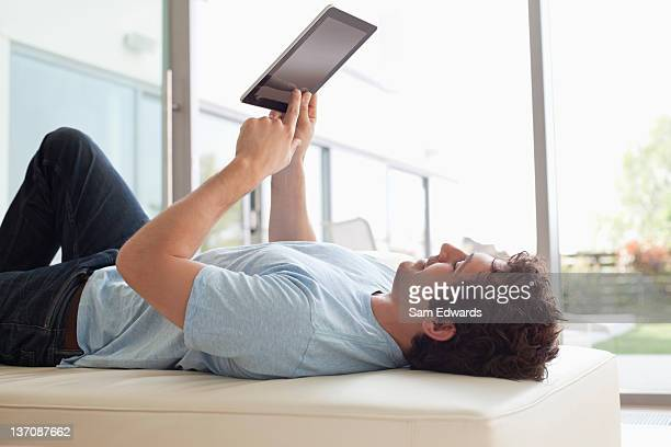 man laying down using digital tablet - convenience stock photos and pictures