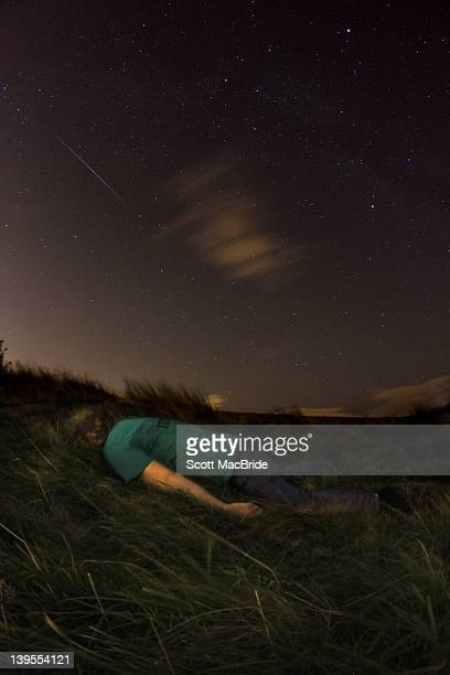 man laying face down on some grass - scott macbride stock pictures, royalty-free photos & images