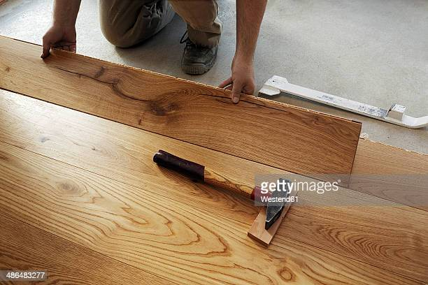 Man laying finished parquet flooring, close-up