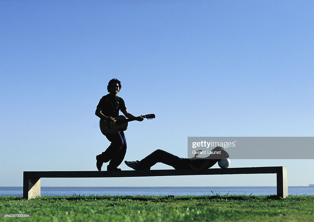 Man laying guitar, woman lying on bench near water. : ストックフォト